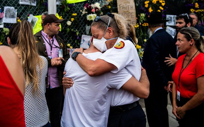 """A member of the Miami-Dade Fire Department hugs a family member of the victims at the """"Surfside Wall of Hope & Memorial"""" near the site where a building collapsed - CHANDAN KHANNA /AFP"""