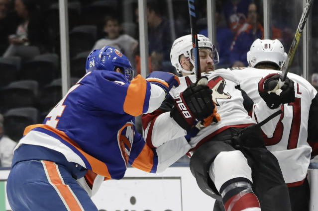 New York Islanders' Scott Mayfield (24) checks Arizona Coyotes' Derek Stepan (21) during the first period of an NHL hockey game Thursday, Oct. 24, 2019, in Uniondale, N.Y. (AP Photo/Frank Franklin II)