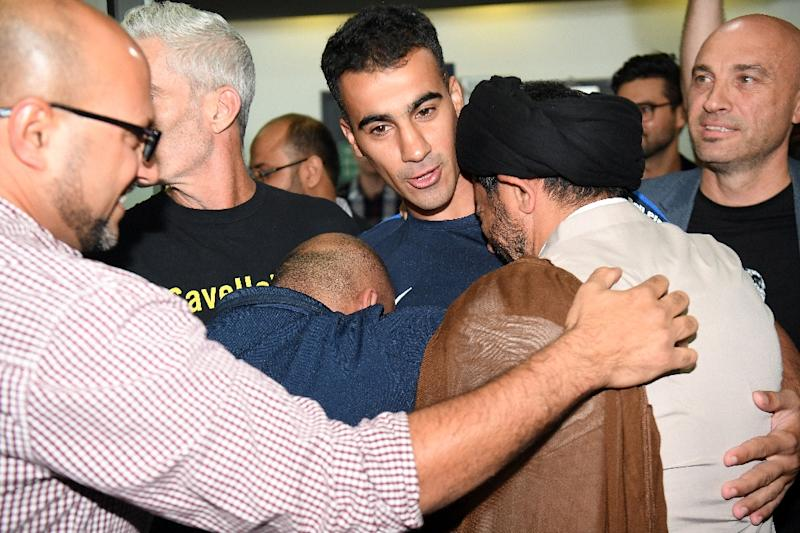 Hakeem al-Araibi (C) was greeted by a throng of well wishers at Melbourne Airport after an overnight flight to freedom (AFP Photo/WILLIAM WEST)