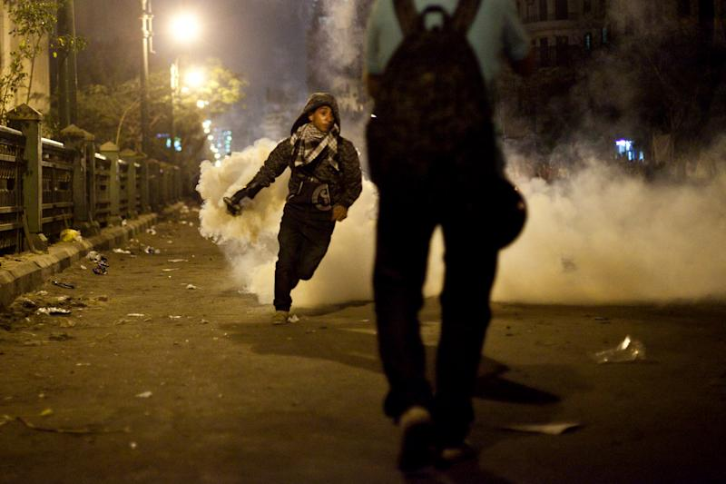 A protester throws away a tear gas canister fired by security forces in downtown Cairo, Egypt, Saturday, April 6, 2013. Police fired tear gas at hundreds of protesters outside the chief prosecutor's office Saturday in central Cairo after they tried to push on the building's doors demanding he resign.(AP Photo/Virginie Nguyen Hoang)