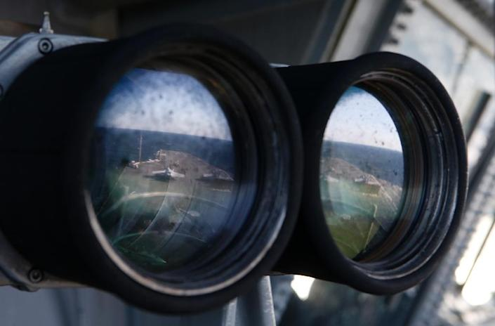 The deck of the USS Ronald Reagan, a Nimitz-class nuclear-powered aircraft carrier, is reflected in a pair of binoculars during a joint naval drill between South Korea and the US (AFP Photo/Kim Hong-Ji)