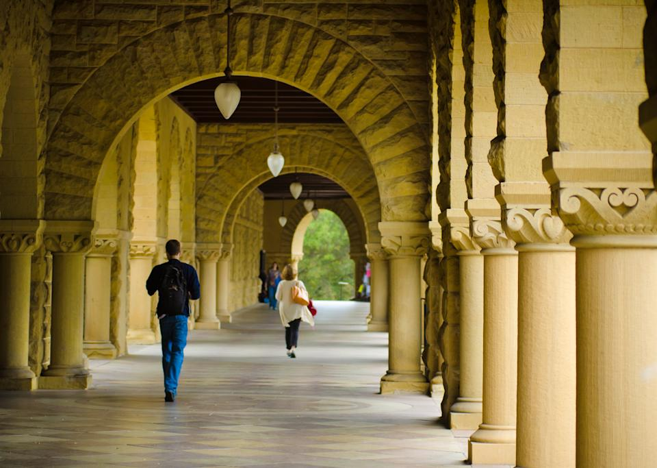 Stanford, United States - October 10, 2011: Students walk underneath a covered walkway at the Stanford University campus on their way to classes. Originally established in 1891, the university has over 15,000 students.