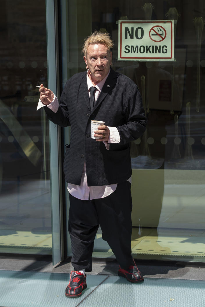 John Lydon, also known as Johnny Rotten, outside the Hight Court Rolls Building in London, where he is giving evidence in a hearing between two former Sex Pistols band members and the band frontman over the use of their songs in a television series, Wednesday July 21, 2021. Drummer Paul Cook and the band's former guitarist, Steve Jones, are suing the Pistols' former lead singer to allow their songs to be used in a TV series. (Dominic Lipinski/PA via AP)