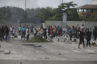 People protest against alleged police brutality, near the Lekki toll gate in Lagos, Nigeria, Wednesday Oct. 21, 2020. After 13 days of protests against alleged police brutality, authorities have imposed a 24-hour curfew in Lagos, Nigeria's largest city, as moves are made to stop growing violence. ( AP Photo/Sunday Alamba)