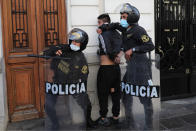 Police detain a protester near Congress where lawmakers swore-in a new president after voting to oust President Martin Vizcarra the day before, in Lima, Peru, Tuesday, Nov. 10, 2020. Peru swore in businessman and head of Congress Manuel Merino Tuesday who is unknown to most and was recently accused of trying to secure the military's support for a congressional effort to boot the nation's last leader out over unproven corruption allegations. (AP Photo/Rodrigo Abd)