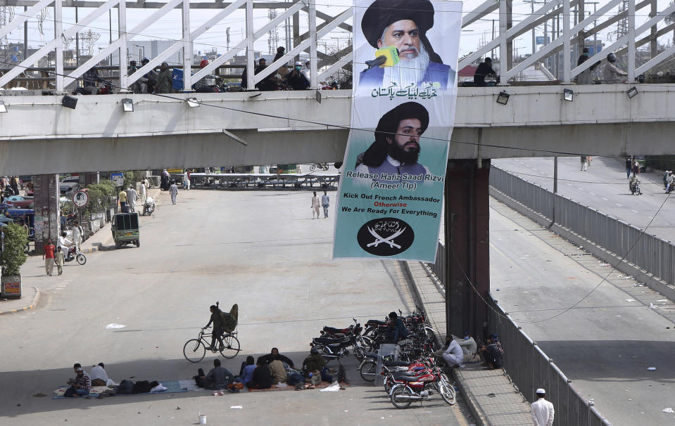 A banner with the portraits of Khadim Hussein Rizvi, top, and Saad Rizvi, leaders of Tehreek-e-Labiak Pakistan, a radical Islamist political party, hang on a bridge while their supporters block a road during a sit-in protest against the arrest of Rizvi, the head of their party, in Lahore, Pakistan, Wednesday, April 14, 2021. Pakistani security forces swinging batons and firing teargas moved before dawn Wednesday to clear sit-ins by protesting Islamists in the garrison city of Rawalpindi and elsewhere after five people died in earlier clashes, officials said. (AP Photo/K.M. Chaudary)