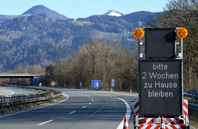 """""""Please stay home for two weeks,"""" reads a sign on a highway near the Austrian-German border"""