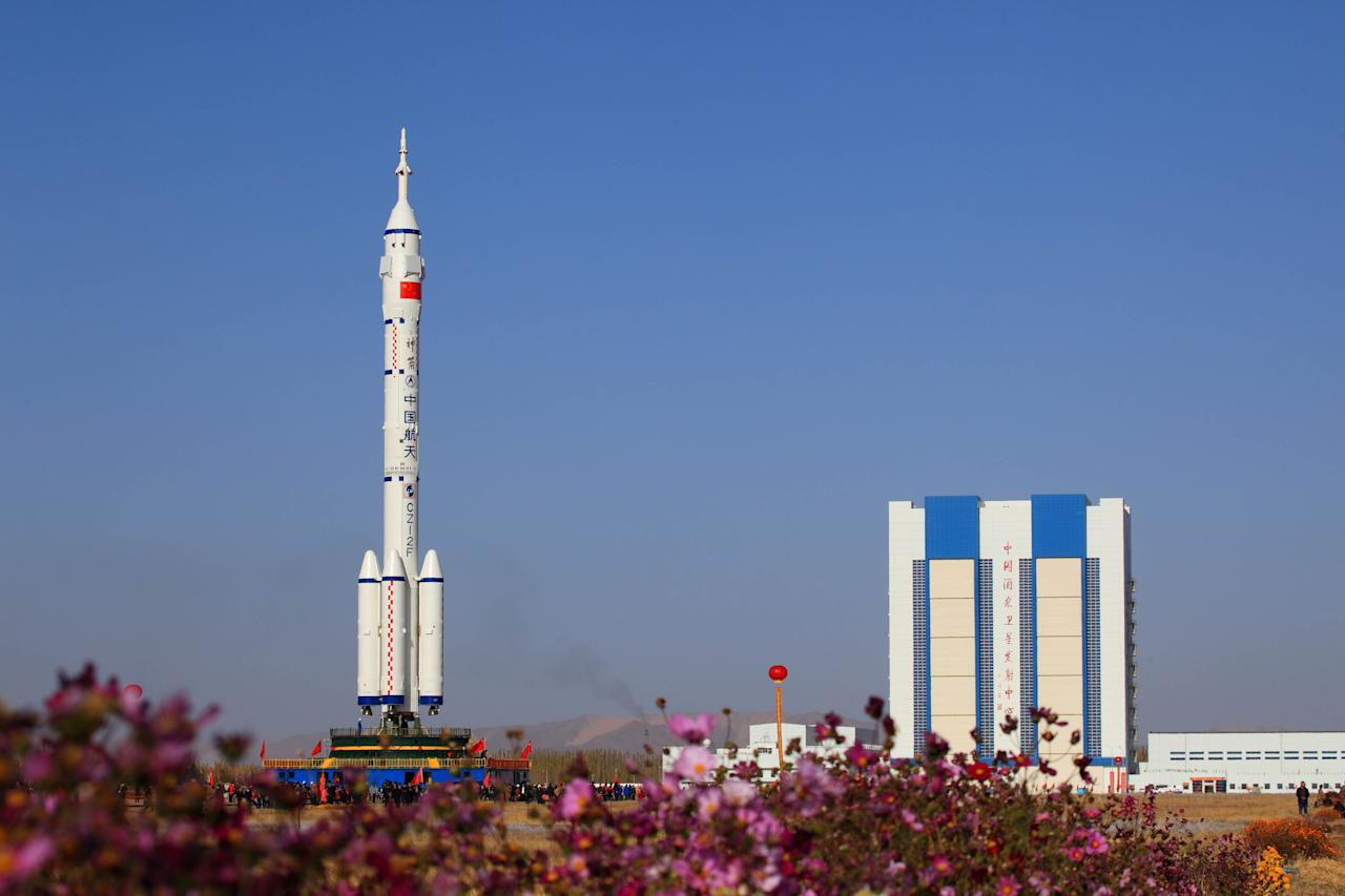 JIUQUAN, CHINA - OCTOBER 26:  (CHINA OUT) An upgraded Long March 2F rocket carries the Shenzhou-8 spacecraft at the Jiuquan Satellite Launch Center on October 26, 2011 in Jiuquan, China. The Shenzhou-8 spacecraft is scheduled to launch in early November, on a space mission to dock with China's first unmanned space module Tiangong-1.  (Photo by ChinaFotoPress/Getty Images)
