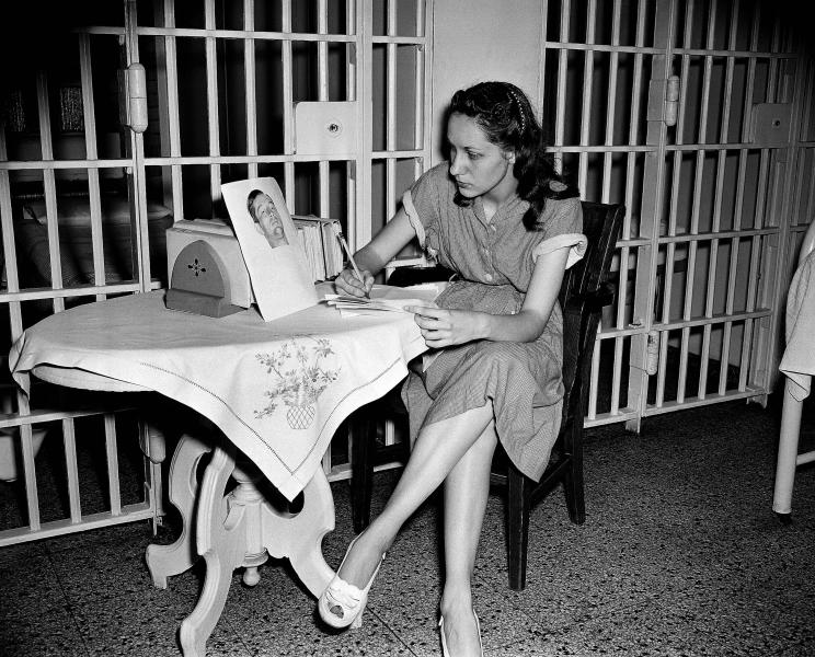 """FILE - In this June 18, 1949 file photo, Ruth Steinhagen, 19, held in the shooting of Philadelphia Phillies first baseman Eddie Waitkus at a Chicago hotel on June 14, 1949, writes notes for her life history in Cook County Jail in Chicago. At the table she has a photograph of Waitkus taken June 17 in the hospital where he was recovering from a bullet wound. Steinhagen died of natural causes at 83 in late December 2012. Her death is the final chapter in one of the most sensational and bizarre criminal cases in Chicago history that made headlines around the country. She was the inspiration for Bernard Malamud's novel """"The Natural"""" and the 1984 movie starring Robert Redford. (AP Photo/File)"""