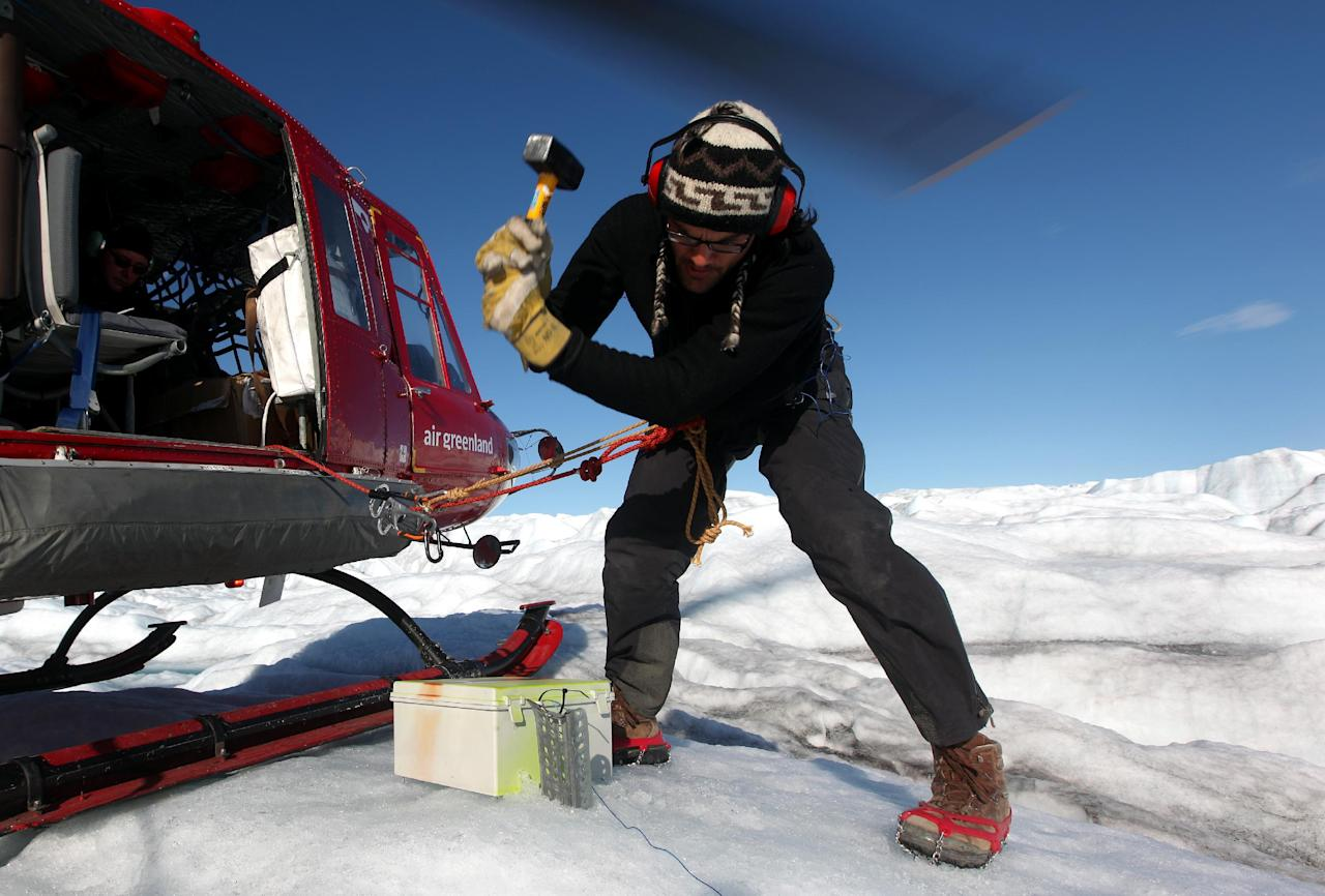 FOR STORY GROENLANDIA-CALENTAMIENTO - FILE - In this July 19, 2011 file photo, attached by rope to a waiting helicopter, Arctic researcher Carl Gladish of New York University hammers a steel stake into ice, securing a newly-deployed GPS seismometer, or Geopebble, designed to track glacial movement near the edge of the Greenland ice sheet, atop Jakobshavn Glacier, outside Ilulissat, Greenland. The chief researcher, NYU's David Holland, hopes to eventually deploy scores of the devices to help measure ice loss in Greenland. (AP Photo/Brennan Linsley, File)