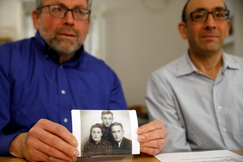 Brothers Eli and Saul Lieberman show a photograph of their late father Joseph, a survivor of the Nazi death camp Auschwitz, taken several years after the Holocaust, during an interview with Reuters in Jerusalem