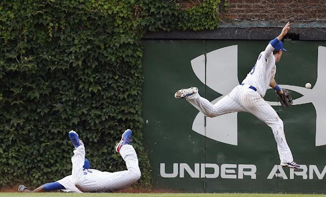 10ThingstoSeeSports - Chicago Cubs center fielder Junior Lake, left, and left fielder Chris Coghlan, right, miss the catch on a double hit by Atlanta Braves' Jason Heyward during the ninth inning of a baseball game on Friday, July 11, 2014, in Chicago. (AP Photo/Andrew A. Nelles, File)