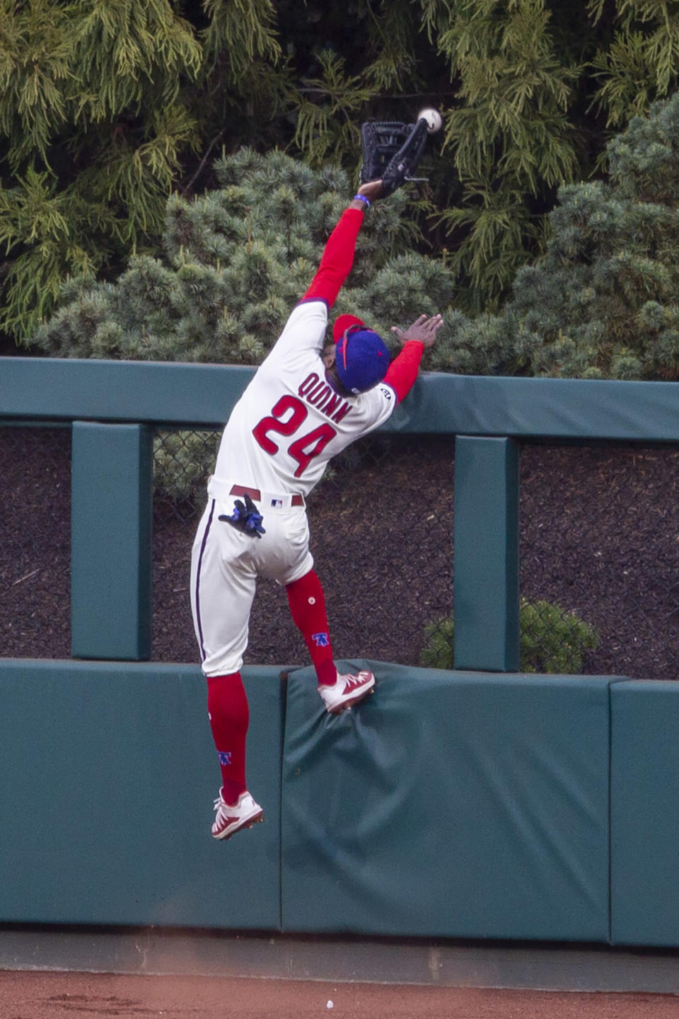 Philadelphia Phillies center fielder Roman Quinn goes over the fence trying to catch a home run by St. Louis Cardinals' Paul DeJong (11) during the third inning of a baseball game, Saturday, April 17, 2021, in Philadelphia. (AP Photo/Laurence Kesterson)