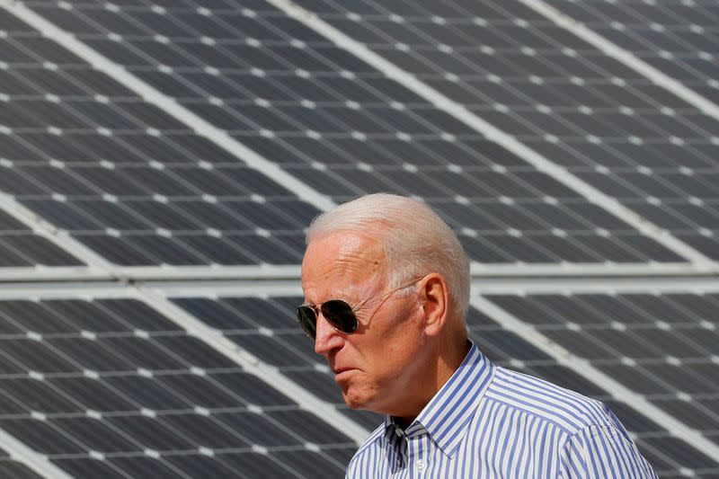 FILE PHOTO: Democratic 2020 U.S. presidential candidate Biden walks past solar panels in Plymouth