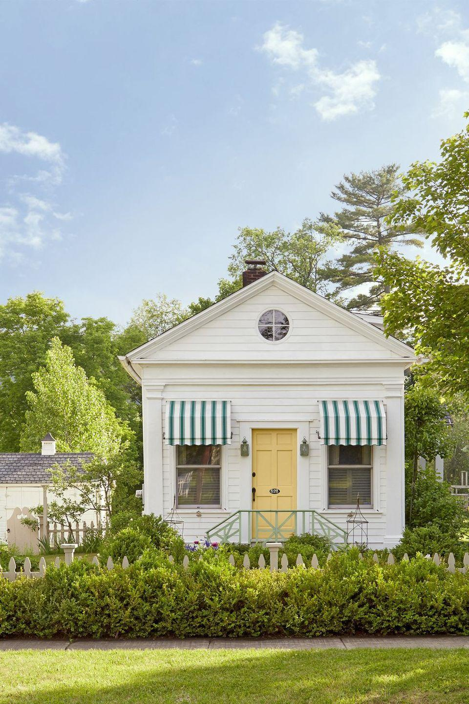 """<p>It doesn't get much cuter than this tiny schoolhouse-turned-cottage with its yellow door and striped green awnings.</p><p><a class=""""link rapid-noclick-resp"""" href=""""https://store.benjaminmoore.com/storefront/color-samples/paint-color-samples-1-pint/prodPRM01A.html?sbcColor=340"""" rel=""""nofollow noopener"""" target=""""_blank"""" data-ylk=""""slk:SHOP YELLOW PAINT"""">SHOP YELLOW PAINT</a></p>"""