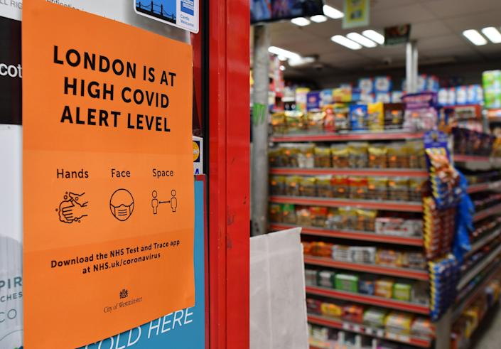 "A convenience store displays a sign informing customers that London is at a ""High"" Covid alert level in the Soho district of London on October 18, 2020, as further restrictions come into force to combat the rising numbers of novel coronavirus covid-19 cases. - Britain's pub industry is bearing the brunt of new restrictions introduced to combat rising coronavirus infection rates. Soaring rates in north-west England have forced stringent restrictions, with pubs only allowed to serve alcohol as part of sit-down meals. (Photo by JUSTIN TALLIS / AFP) (Photo by JUSTIN TALLIS/AFP via Getty Images)"