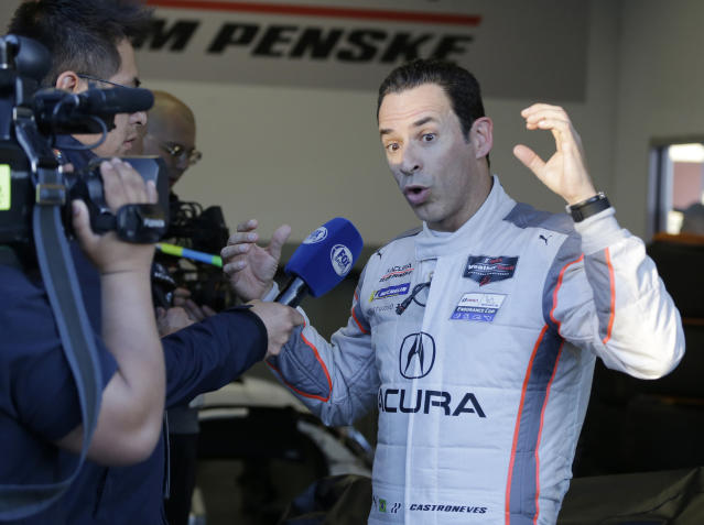 Acura Team Penske driver Helio Castroneves talks to a TV crew while his crew makes repairs to damage from a crash during the Rolex 24 hour auto race at Daytona International Speedway, Saturday, Jan. 25, 2020, in Daytona Beach, Fla. (AP Photo/Terry Renna)