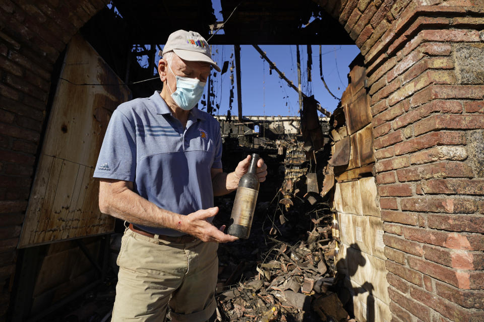 "Dario Sattui holds one of the more than 100,000 bottles of wine lost when fire devoured a building near his Tuscan-style castle, Castello di Amorosa in Calistoga, Calif., on Thursday, Oct. 15, 2020. ""I've been in the wine business for 48 years and this is by far the most catastrophic, devastating, most horrible year,"" said Sattui. (AP Photo/Eric Risberg)"