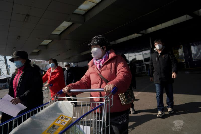 Customers wearing face masks leave a supermarket, as the country is hit by an outbreak of the novel coronavirus, in Beijing