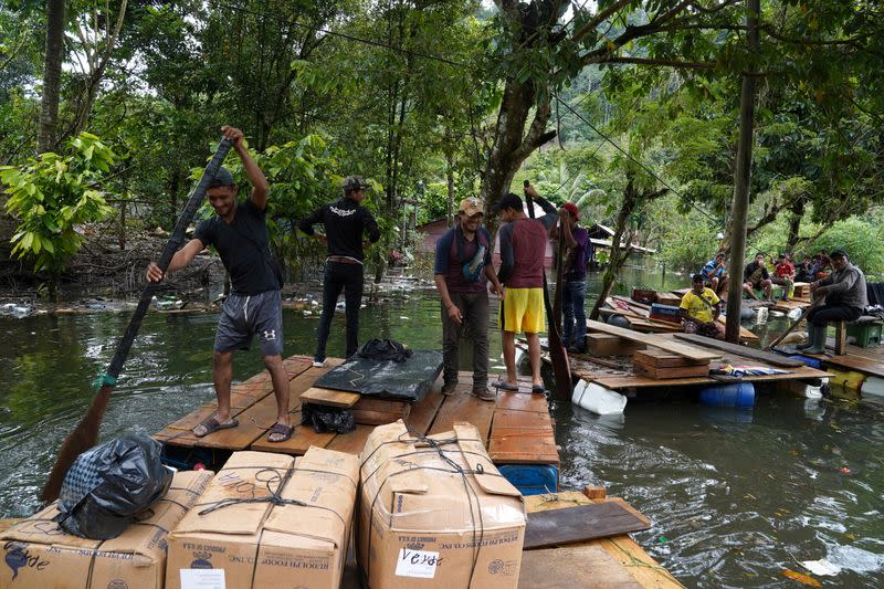 Residents use rafts made of wooden crates and empty containers to transport people and goods through flooded areas affected by Hurricanes Eta and Iota, in Alta Verapaz