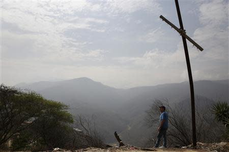 Auto mechanic Juan Freire looks at a valley, where a housing development was meant to be built, at El Chaparral commune in La Guaira May 2, 2014. REUTERS/Carlos Garcia Rawlins