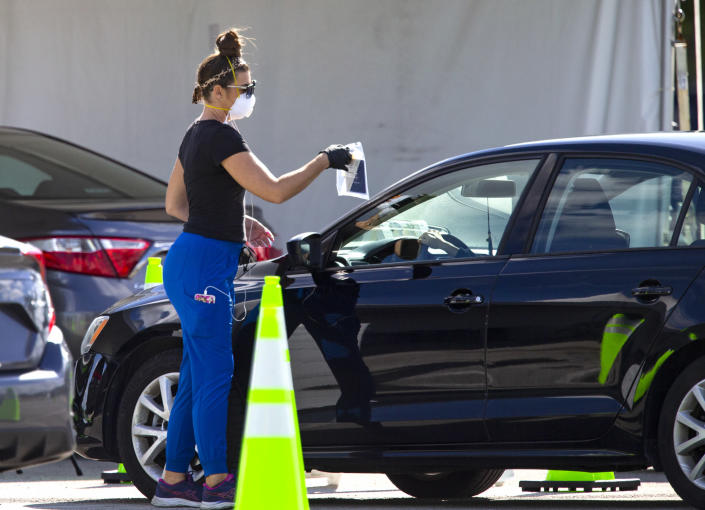 A health care worker direct a person to use a swab for a self administered test at the Miami-Dade County Youth Fairgrounds at Tamiami Park, on Sunday, Nov. 29, 2020 in Miami. (David Santiago/Miami Herald via AP)