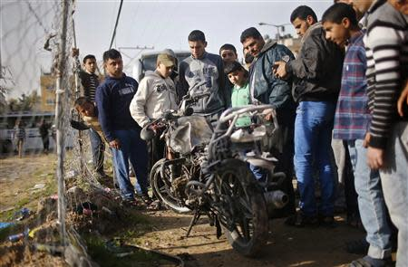 Palestinians look at a motorcycle, which witnesses said was hit in an Israeli air strike, in the northern Gaza Strip January 19, 2014. REUTERS/Mohammed Salem