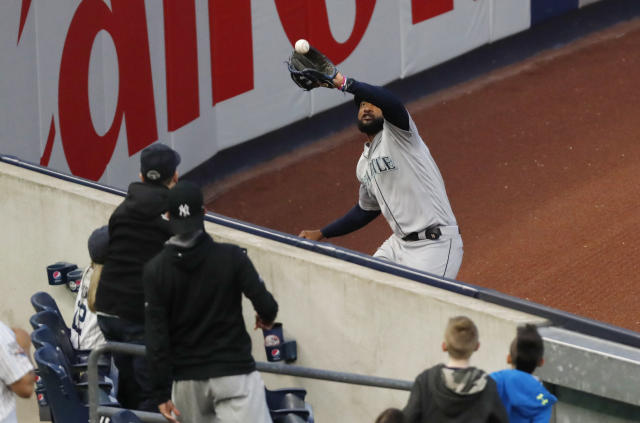 Seattle Mariners left fielder Domingo Santana catches a fly ball by New York Yankees' Miguel Andjuar during the fourth inning of a baseball game Tuesday, May 7, 2019, in New York. (AP Photo/Kathy Willens)