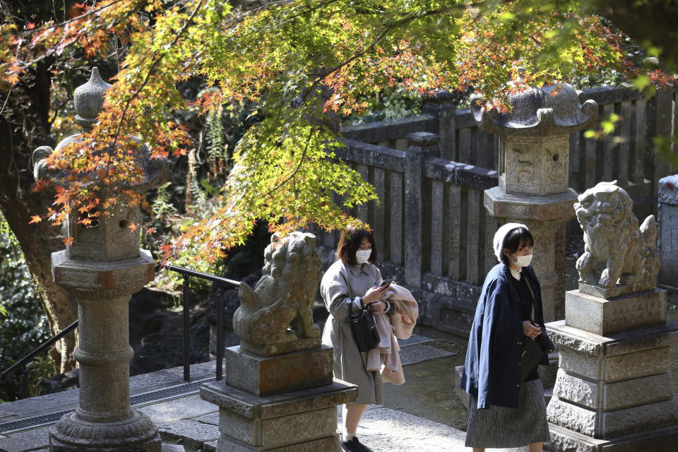 Visitors wearing face masks to protect against the spread of the coronavirus walk through the colorful autumn leaves at the Kenchoji temple in Kamakura, Monday, Nov. 30, 2020. (AP Photo/Koji Sasahara)