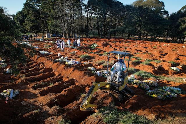 14 October 2020, Brazil, Sao Paulo: An excavator digs more graves at the Vila Formosa cemetery in the middle of the Corona pandemic. The Ministry of Health has confirmed 955 377 Covid-19 infected and 46 510 coronavirus deaths. More than a quarter of the newly registered deaths occurred in the state of São Paulo. Photo: Lincon Zarbietti/dpa (Photo by Lincon Zarbietti/picture alliance via Getty Images)