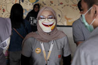 An employee wearing a face mask as a precaution against the new coronavirus outbreak shares a light moment with colleagues at a McDonald's restaurant in Jakarta, Indonesia, Sunday, May 10, 2020. (AP Photo/Dita Alangkara)