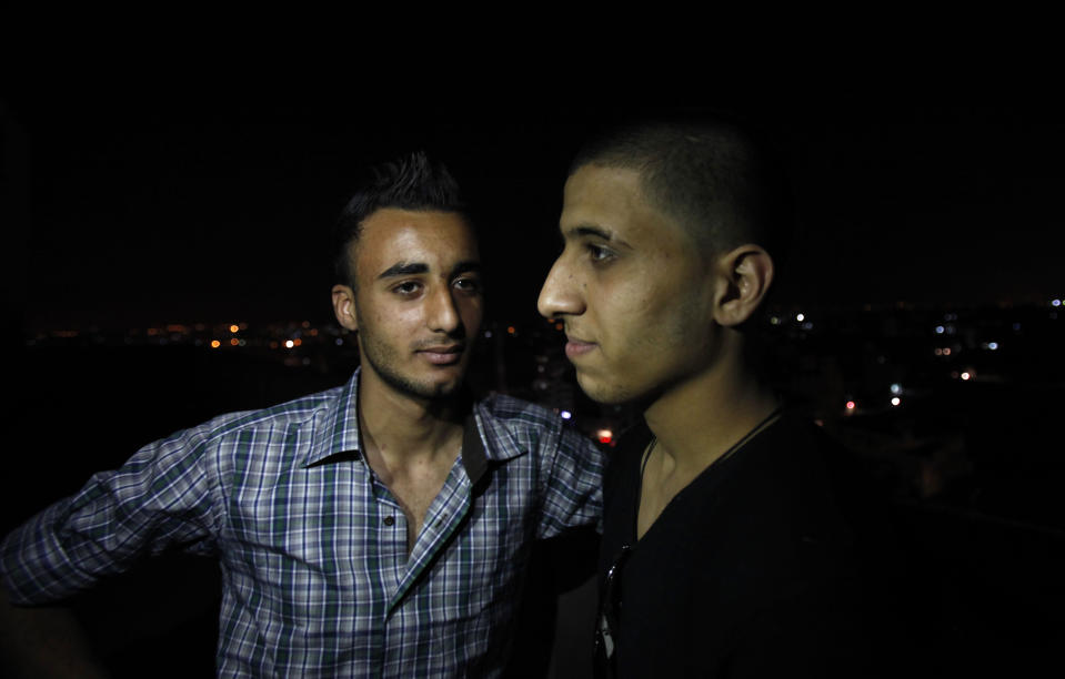Mohammed Hanouna, 18, left, looks at his friend Ayman al-Sayed, 19, right, with his hair cut, in Gaza City, Sunday, April 7, 2013. Al-Sayed used to have shoulder-length hair but says he was grabbed by Hamas police in a sweep along with other young men with long or gel-styled spiky hair last week, and that police shaved everyone's head. Hanouna still wears the hair-style that can now get young men in trouble in Gaza, during the Islamic militants latest attempt to impose their hardline version of Islam on Gaza. (AP Photo/Adel Hana)