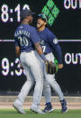 Seattle Mariners right fielder Dillon Thomas (27) celebrates with center fielder Taylor Trammell (20) after going up against the scoreboard to catch a fly ball hit by Detroit Tigers' Niko Goodrum during the second inning of a baseball game Wednesday, June 9, 2021, in Detroit. (AP Photo/Duane Burleson)