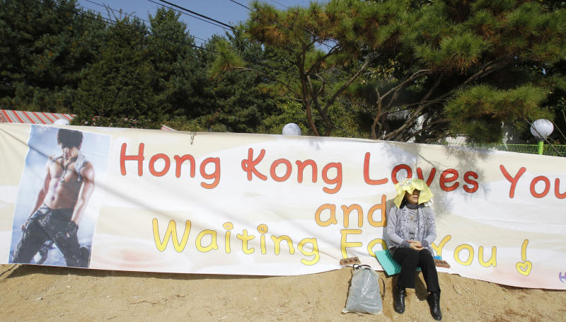 A fan from Hong Kong waits for South Korean pop singer Rain before the 29-year-old enters the army to serve in front of an army training center in Uijeongbu, north of of Seoul, South Korea, Tuesday, Oct. 11, 2011. (AP Photo/ Lee Jin-man)