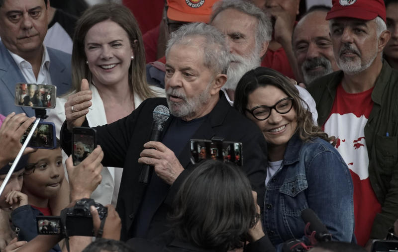 Brazil's former President Luiz Inacio Lula da Silva speaks to supporters as his girlfriend Rosangela da Silva leans on his back after he was released from Federal Police headquarters where he was imprisoned on corruption charges in Curitiba, Brazil, Friday, Nov. 8, 2019. Da Silva walked out of the Curitiba prison Friday, less than a day after the Supreme Court ruled that a person can be imprisoned only after all the appeals have been exhausted. (AP Photo/Leo Correa)