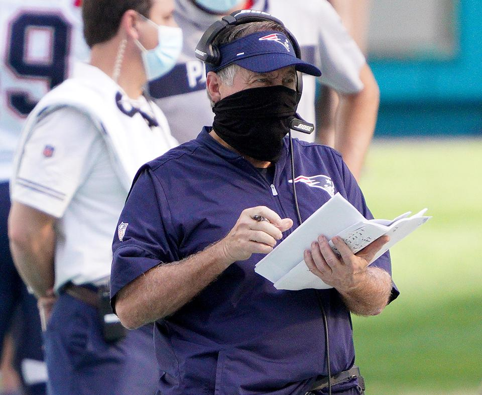 Bill Belichick wears a mask, visor and headset while he holds a stack of papers and looks on during the game against the Dolphins.