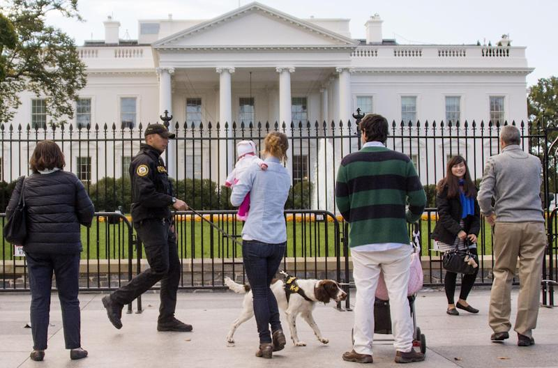 A US Secret Service Uniformed Division officer and his K-9 dog patrol the fence line of the White House in Washington, DC, October 23, 2014 (AFP Photo/Jim Watson)