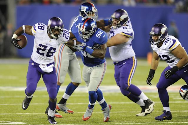 Minnesota Vikings running back Adrian Peterson (28) breaks a tackle by New York Giants' Jon Beason (52) as Jerome Felton (42) trails the play during the second half of an NFL football game Monday, Oct. 21, 2013 in East Rutherford, N.J. (AP Photo/Bill Kostroun)