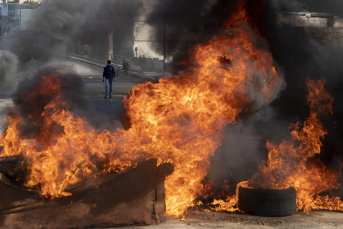 Protesters burn tires to close a main road, after the Lebanese pound hit a record low against the dollar on the black market, in Beirut, Lebanon, Saturday, March 6, 2021. (AP Photo/Hassan Ammar)