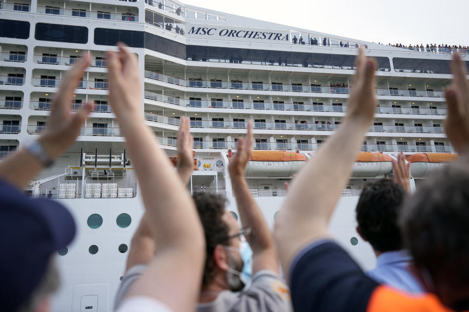 """People applaud as the 92,409-ton, 16-deck MSC Orchestra cruise ship departs from Venice, Italy, Saturday, June 5, 2021. The first cruise ship leaving Venice since the pandemic is set to depart Saturday amid protests by activists demanding that the enormous ships be permanently rerouted out the fragile lagoon, especially Giudecca Canal through the city's historic center, due to environmental and safety risks. The cruiser passed two groups of protesters: pro-cruise advocates whose jobs depend on the industry as well as protesters belonging to a movement called """"No Big Ships"""" who have been campaigning for years to get cruise ships out of the lagoon. (AP Photo/Antonio Calanni)"""