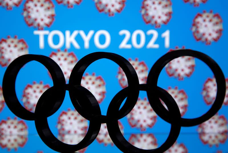 """A 3D printed Olympics logo is seen in front of displayed """"Tokyo 2021"""" words in this illustration"""