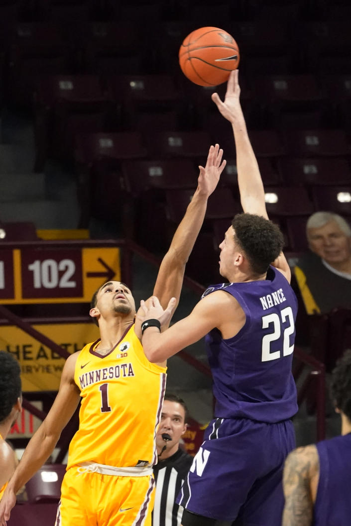 Northwestern's Pete Nance (22) shoots over Minnesota's Tre' Williams (1) in the first half of an NCAA college basketball game, Thursday, Feb. 25, 2021, in Minneapolis. (AP Photo/Jim Mone)