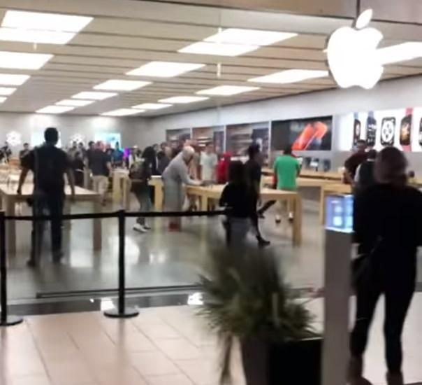 Customers stood by and watched as a group of young men pulled an Apple store theft in broad daylight - sprinting away with a computer and other devices. (Twitter/Gooneryoda)