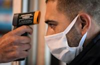 A bus driver has his temperature checked before his shift in a parking and carwash, in Buenos Aires, on April 17 amid the coronavirus pandemic