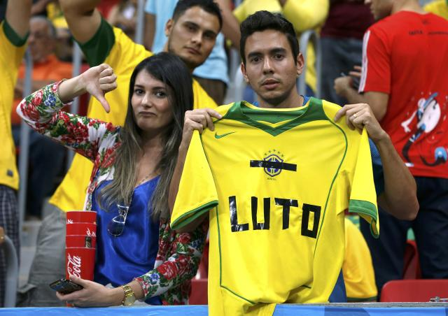 "Fans hold up a Brazil jersey reading, ""Mourn"" during the 2014 World Cup third-place playoff between Brazil and the Netherlands at the Brasilia national stadium in Brasilia July 12, 2014. REUTERS/Jorge Silva (BRAZIL - Tags: SOCCER SPORT WORLD CUP)"