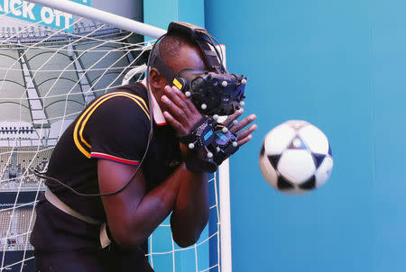 Gold Coast 2018 Commonwealth Games - Gold Coast, Australia - April 12, 2018. Former Jamaican sprinter Usain Bolt plays with a ball while wearing a VR headset. REUTERS/David Gray