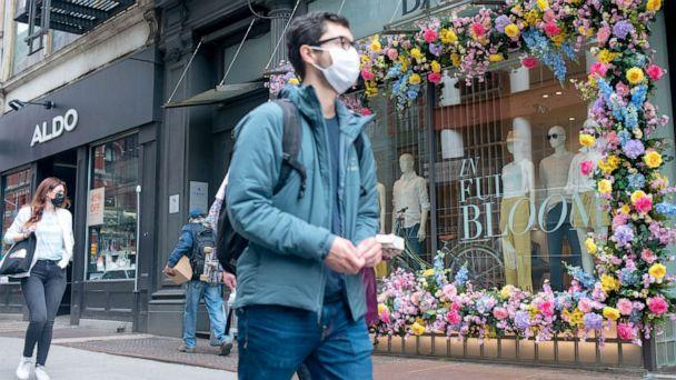 PHOTO: Pedestrians wear masks as they walk past a flower decoration at Banana Republic in the SoHo neighborhood of New York, March 25, 2021. (Alexi Rosenfeld/Getty Images)