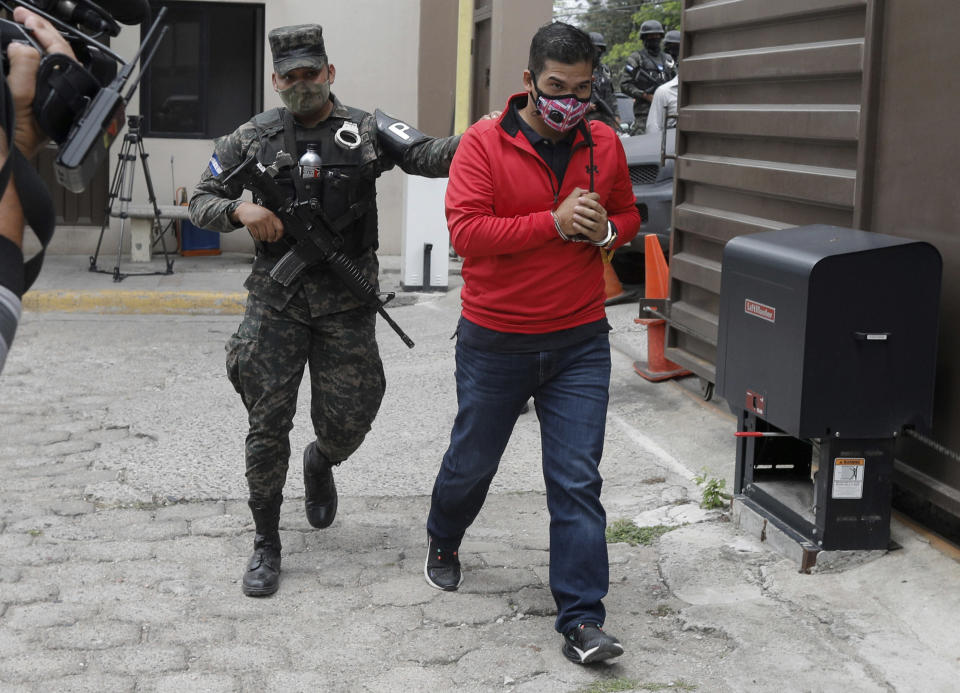 An alleged mastermind of the murder of Honduran environmental and Indigenous rights activist Berta Caceres, Roberto David Castillo is escorted by a police officer upon his arrival to the Supreme Court in Tegucigalpa, Honduras, Tuesday, April 6, 2021. Catillo's trial began five years after the prize-winning activist's murder. (AP Photo/Elmer Martinez)