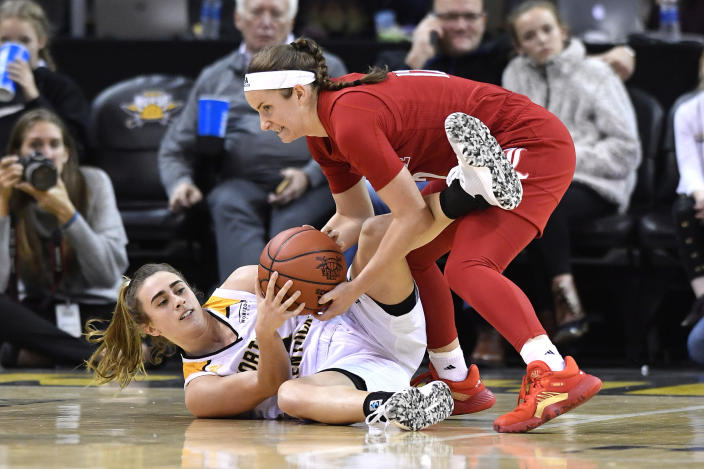 Louisville guard Lindsey Duvall (12), top, battles Northern Kentucky guard Carissa Garcia (12) for a loose ball during the second half of an NCAA college basketball game in Highland Heights, Ky., Sunday, Dec. 8, 2019. Louisville won 85-57. (AP Photo/Timothy D. Easley)