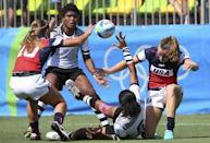 <p>Tinaima Tamoi of Fiji is tackled by Richelle Stephens and Ryan Carlyle of USA. (Reuters) </p>